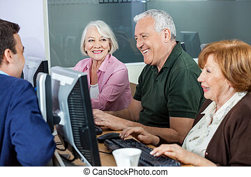 Happy Senior Students Discussing With Teacher In Computer Class