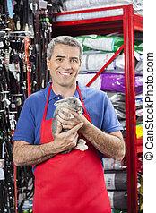 Happy Salesman Holding Rabbit In Pet Store - Portrait of...
