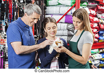 Smiling Family And Saleswoman Looking At Guinea Pig -...