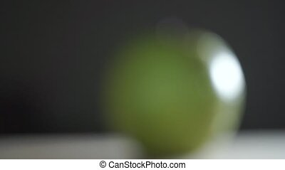 Man hand placing wet green apple and cutting it with a big...