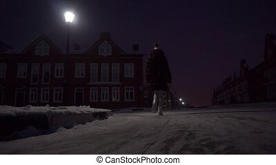 Young woman in fur coat walking on crispy snow in residential area at night