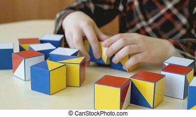 Child collecting a pattern using colored cubes - Child...