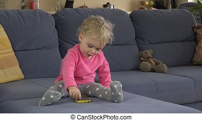 Babysitter help cute baby girl to use smart phone sitting on...