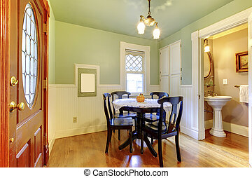 Small and cozy dining room with black wood table chair set and green walls connected with bathroom