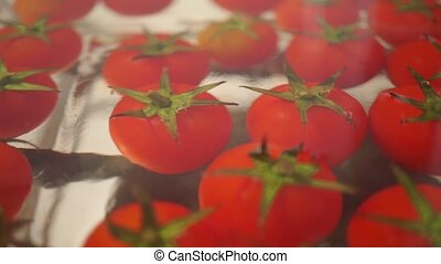 Red cherry tomatoes in a glass pan on a stove, dolly shot