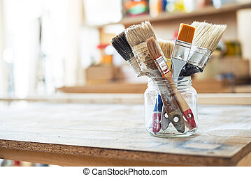 Paint brushes on the table in a workshop.