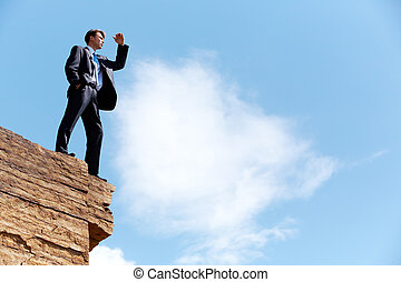 Solitude - Photo of happy businessman standing on the cliff...
