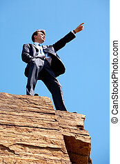 On high cliff - Photo of serious businessman standing on the...