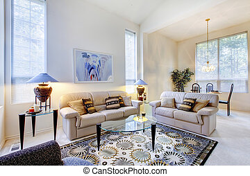 Bright white and blue living room with glass coffee table and rug.