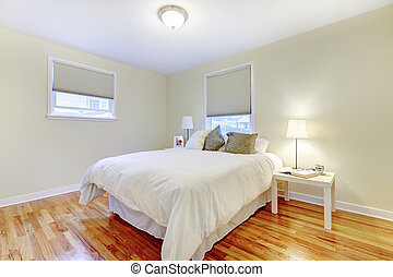 Simplistic white and brown bedroom interior with hardwood floor and beige walls.