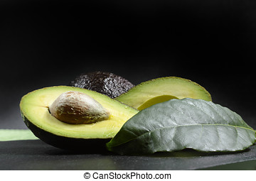 Fresh ripe organic avocado on green and black background