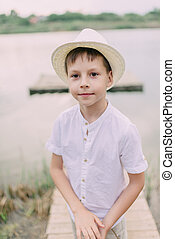 boy in hat near the river