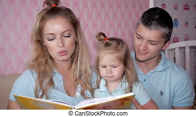 Young parents read the book to children at home. Mother Father and Daughter reading.