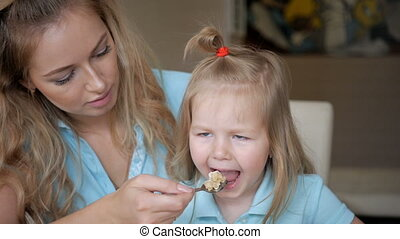 Young mother feeds her young child from a spoon. Oatmeel breakfast with mother and daughter.