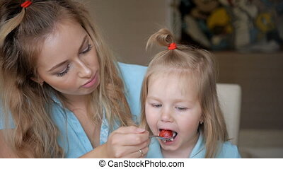 Young mother feeds her young child from a spoon. Oatmeel...