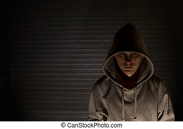 Troubled Youth - Youth in hooded top in front of garage door...