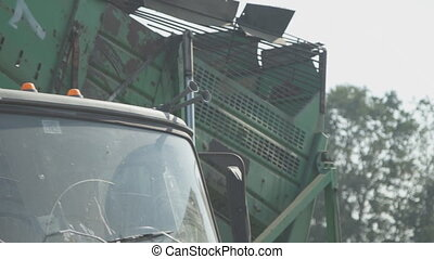 Potato harvester on conveyor belt delivers crop in truck.