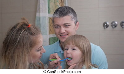Mother and father teaching little daughter clean teeth