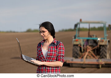 Farmer girl with laptop in field with tractor - Young happy...