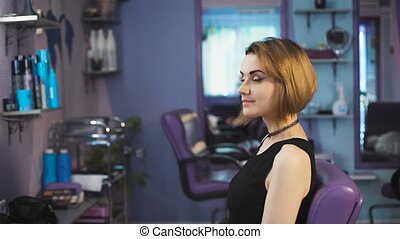 Beautiful brown-haired woman in a beauty salon appreciates...