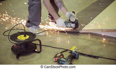 View of man saw up metal springboard in skatepark. Many bright sparks. Preparing to competition.