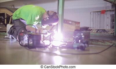 Welder in protective mask, green shirt welding metal balks...