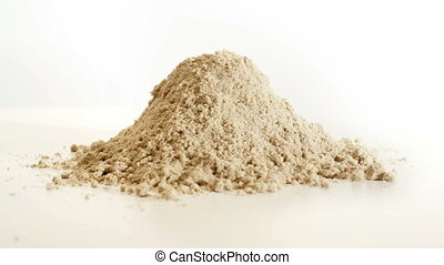 A pile of sand crumbles and becomes flat. It has a white...