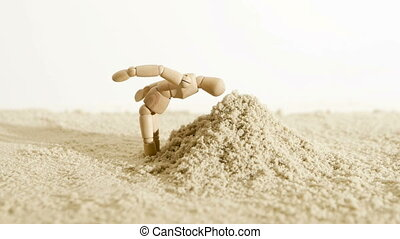 A wooden man buries his head in the sand and then continues...