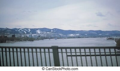 Car driving on bridge above wide river. View of landscape with snow mountains. Buildings. Traveling