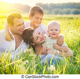 Happy joyful young family with little sons having fun outdoors