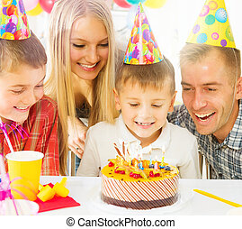 Birthday Little boy blows out candles on birthday cake