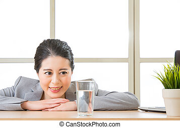 Young asian businesswoman looking at glass of water