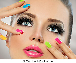 Beauty girl face with colorful nail polish. Manicure and...