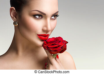 Fashion model girl with red rose in her hand
