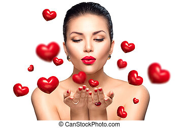 Beauty woman with perfect makeup blowing Valentine hearts
