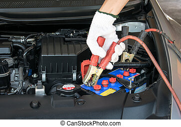 automotive technician charging vehicle battery