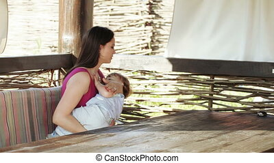 Mama cradles baby on nature - On wooden bench on nature...