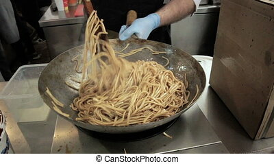 Fry the noodles in the pan - Cook stirs the noodles in the...