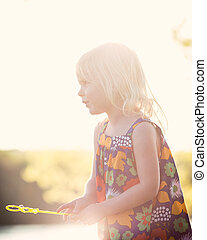 Sunflare caucasian girl playing at sunset with bubbles -...