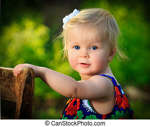 Little caucasian toddler stands using chair for support outside