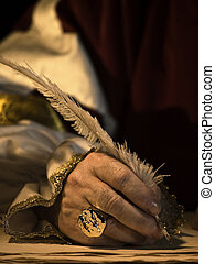 Quill and Signet Ring - A senior mans hand holding a quill...