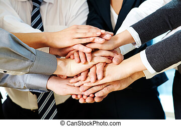 Strength - Image of business partners hands on top of each...
