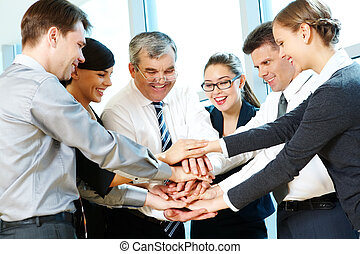 Support - Photo of smiling co-workers making pile of hands...