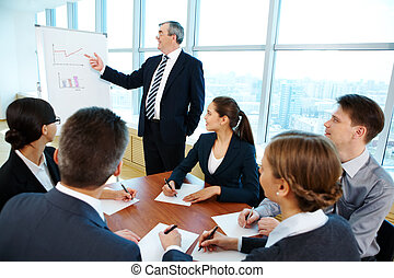 Seminar - Smart and confident boss pointing at whiteboard...