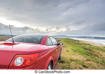 Red car on the beach.
