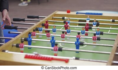 Men playing table soccer on street Summer festival...