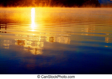 beautiful reflection of sun at down in golden morning fog.