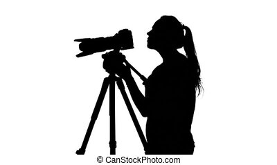 Photographer spends shooting video. White. Silhouette -...
