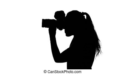 Photographer looks at the camera. White. Silhouette -...
