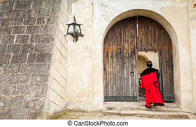 Open door of old castle - Man in ancient cloth enters into...